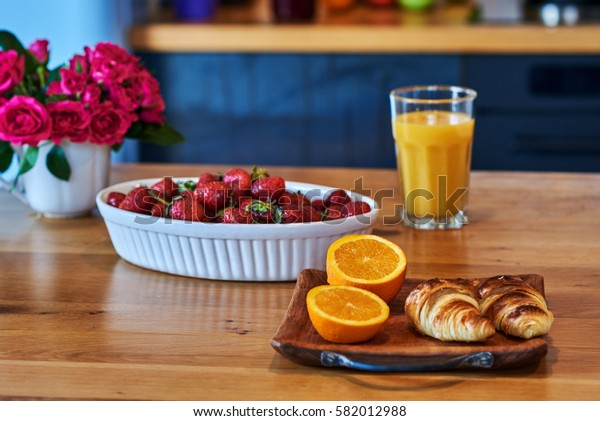 Rustic wooden background with croissant, fruit  and  flowers. White vintage dinnerware. Breakfast at summer morning.