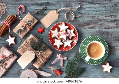 Rustic wooden background with cup of hot coffee and gift wrapping of Christmas cookies. Seasonal background shot from above. Flat lay, top view, filtered image. Tag mockup, copy space on the tags.