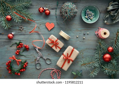 Rustic wooden background in green and red with fir branches, wrapped Xmas gifts and Christmas decorations