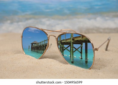 rustic wooden Bahama pier reflected in aviator sunglasses lens on beach sand