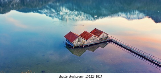 rustic wooden boathouses in the water at sunset beach - aerial drone shot