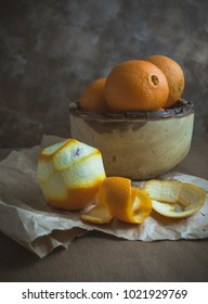 A rustic wooden bowl filled with oranges.  One orange is peeled and sitting on paper with the peel.  The table surface is wood and the background is abstract.
