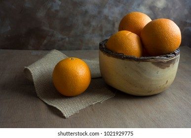A rustic wooden bowl filled with oranges with one orange sitting on burlap.  The table surface is wood and the background is abstract.