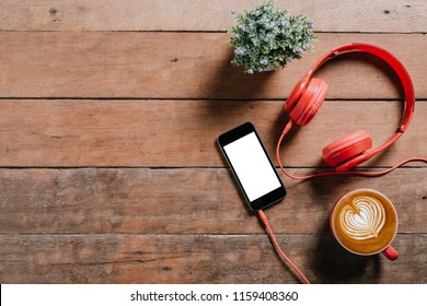 Rustic wooden desk with smart phone,head phone and cup of coffee. Top view with copy space.