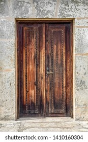 Rustic wooden doors are closed in the old stone wall of Spanish Mission San Juan Capistrano in San Antonio, Texas.
