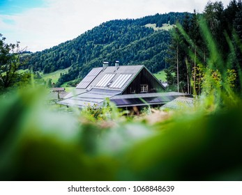 rustic wooden  eco-friendly house with solar panels on the roof surrounded by green nature