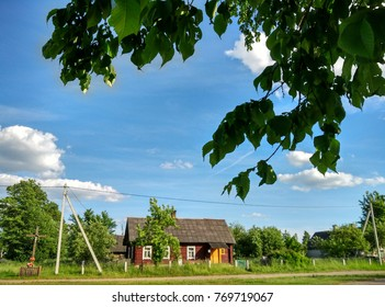 rustic wooden house in the distance, trees and foliage in the foreground