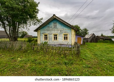 Rustic wooden house. The faded blue paint it is painted with. Old fence. Outbuildings. In the corner is an overgrown mountain ash. The owners rarely come here.