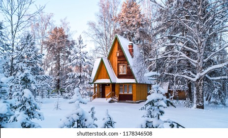 Rustic wooden house in the snow-covered forest. Ural, Russia.