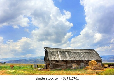 Rustic, wooden, log barn has beautiful mountain view in Happy Valley, Montana.  Barn has wooden roof.