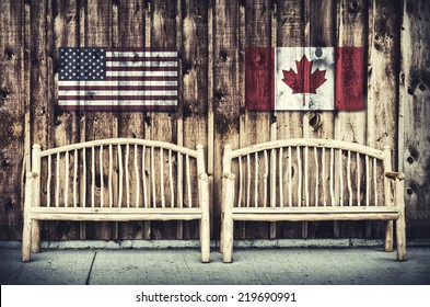 Rustic wooden log benches side by side against a wall of wooden siding with United States of America and Canada flags imprinted above the benches.  Filtered for a retro, vintage look.