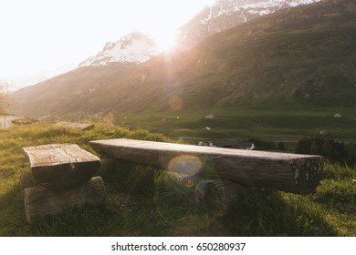 Rustic wooden park bench in the tranquil swiss mountains at sunset