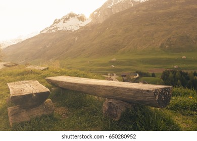 Rustic wooden park bench in the tranquil swiss mountains at sunset light