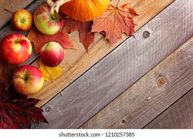 A rustic wooden plank background is bordered by Autumn apples and Fall Sugar Maple Leaves.