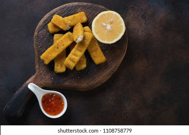 Rustic wooden serving board with fried fish sticks or breaded fish fillet, dark brown metal background with space, high angle view