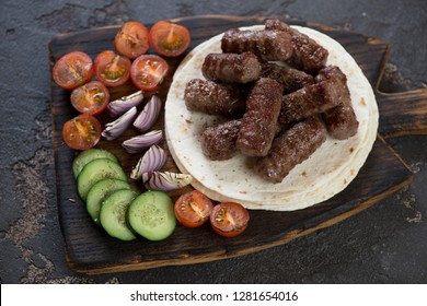 Rustic wooden serving board with grilled cevapi or cevapcici sausages, tortilla wraps and vegetables