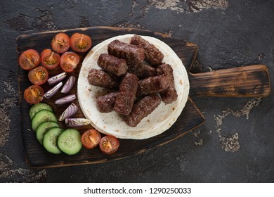 Rustic wooden serving board with grilled cevapi or cevapcici, tortillas and vegetables. Flatlay on a brown stone background
