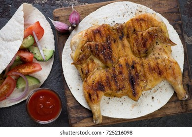 Rustic wooden serving board with roasted chicken tabaka on tortilla bread, view from above