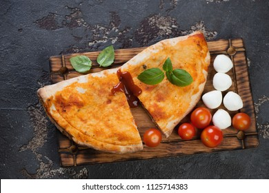 Rustic wooden serving tray with sliced pizza calzone over brown stone background, view from above, horizontal shot