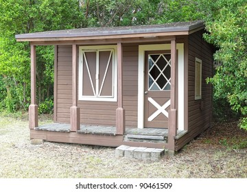Rustic wooden shed with window and front porch at the edge of the forest