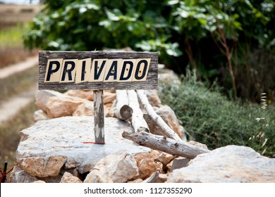Rustic wooden sign with private word in a rural environment of stones and branches