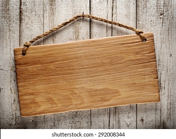 rustic wooden signboard hanging on grunge wall