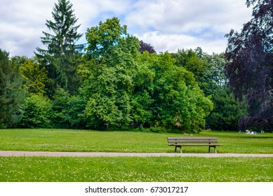 Rustic wooden slatted bench in a verdant green park with neat lawns and woodland trees at the side of a walkway or path