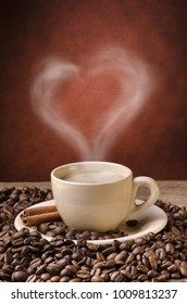 rustic wooden table with coffee beans and a cup of hot coffee from which steam exits forming a heart