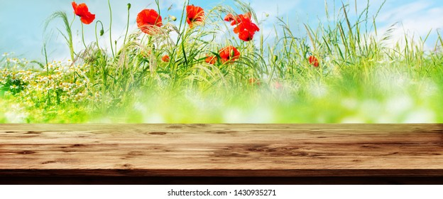 Rustic wooden table and red poppies in a flower meadow for a background