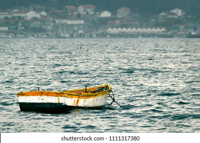 Rustic and yellow fishing boat moored on seashore on a cloudy and stormy day. It represents loneliness.