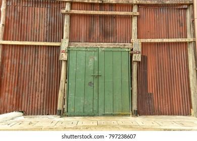 Rustic zinc wall with green wooden door