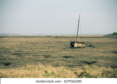 a rusting boat on low tidal grounds in Essex, UK