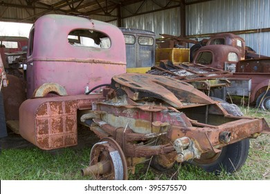 Rusting cab and trailers on old trucks iin aluminum shed.