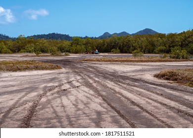 A rusting car wreck on a tidal salt pan environment with tire tracks in the mud