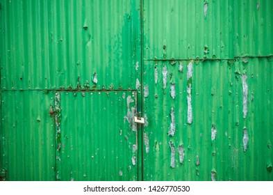 Rusting and flaking green metal garage doors.