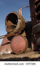 A rusting headlamp of a vintage farm truck.