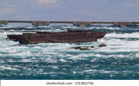 The rusting Niagara Scow above the falls, surrounded by rapids, power dam in the background, blue sky and water.