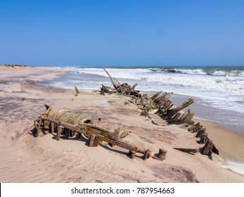The rusting remains of an old shipwreck on the edge of the surf, Skeleton Coast, Namibia.