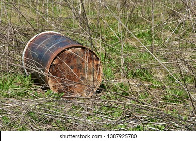 Rusting and rotting 55 gallon steel chemical drum in an wooded area laying on its side.