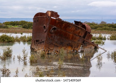 Rusting shipwreck of The Excelsior (1897 - 1945)  partially submerged in the marshland in Mutton Cove Conservation Park, Port Adelaide, South Australia.