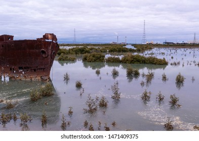 The rusting shipwreck of The Excelsior partially submerged in the mangroves and local industry in the background. Port Adelaide, South Australia.