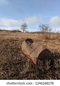 A rusty 55 gallon oil drum spray painted with orange rests in a farm field or meadow on a brisk fall day