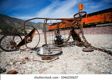 Rusty abandoned wheels and frame with train passing by and blue sky in the background