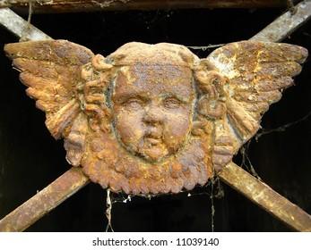 a rusty angel as grave door ornament