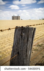 Rusty barbed wire fence with harvested wheat field and grain silo's in background