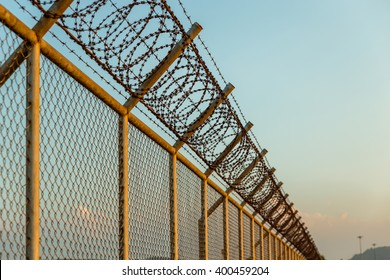rusty barbed wire fence in sunny day