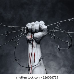 Rusty barbed wire in a strong man's hand