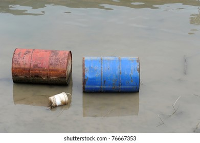 Rusty barrels floating in river, environment pollution concept