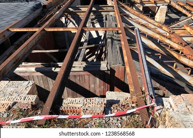 rusty beams on the broken roof of an old house. Open overhead girders covered in rust, view from above. Metal girders of the abandoned building roof. Industrial old weathered rusty steel girders