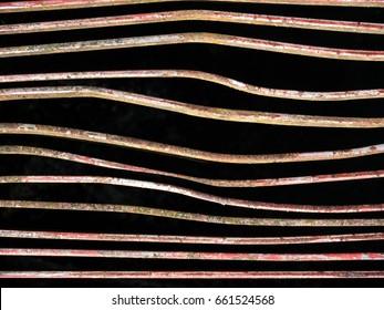 Rusty and bent iron bars on a bridge, black background